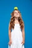 Młody ładny dziewczyny mienia jabłko na głowie nad błękitnym tłem Obrazy Stock