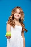 Młody ładny dziewczyny mienia zieleni jabłko nad błękitnym tłem Fotografia Royalty Free
