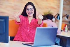 Młody ładny kobieta inżyniera obsiadanie w biurze przy biurkiem z laptopem up i seansu kciukiem ok jak znaka zdjęcie stock