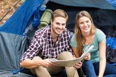 Młody ładny wycieczkowicz pary obsiadanie w namiocie patrzeje kamerę Zdjęcie Stock