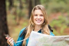 Młody ładny wycieczkowicz używa kompas i mapa patrzeje kamerę Obraz Stock