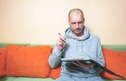 Młody łysy mężczyzna próbuje kalkulować jego roku podatku dług z w przypadkowych ubraniach z śmiesznym, zmieszanym wyrazem twarzy fotografia stock