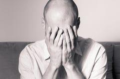 Młody łysy mężczyzna w koszulowej uczucie deprymującej i nędznej pokrywie z jego jego twarz ręki i płacz w jego pokoju obrazy royalty free