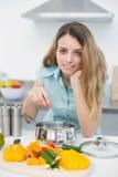Młody śliczny kobiety kucharstwo podczas gdy ono uśmiecha się przy kamerą Fotografia Royalty Free