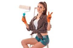 Młody śmieszny brunetki kobiety budowniczy w mundurze z farba rolownikiem w jej rękach robi reovations odizolowywającym na bielu Fotografia Royalty Free