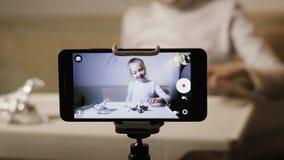Młody, śmieszny dziewczyny blogger, robi rejestrowi zagadnienie Dziecko odpakowywa jajko z niespodzianką zdjęcie wideo