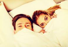 Młody śmieszny pary lying on the beach na łóżku z kołderką na twarzach fotografia stock
