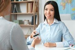 Młody żeński agenta biura podróży konsultant w wycieczki turysycznej agenci z klient zapłatą obraz royalty free