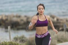 Młody żeński biegacz jogging na chmurnym dniu plażą Obrazy Stock