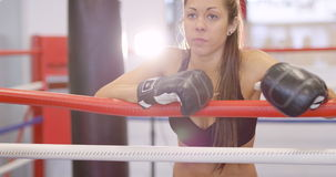 Młody żeński bokser odpoczywa z jej rękami na ringowych arkanach zbiory wideo