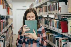 Młody żeński dziewczyna uczeń ono uśmiecha się z książką w bibliotece Zdjęcie Royalty Free