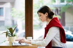 Młody żeński freelancer pracuje z laptopem w spacy pokoju obrazy stock