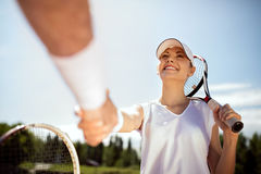 Młody żeński gracz w tenisa wita z trenerem fotografia stock