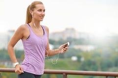 Młody żeński joger jest biegający i słuchający muzyka podczas bieg Obraz Stock