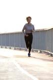 Młody żeński jogger biega outdoors zdjęcia stock