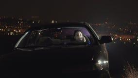Młody żeński kierowca w samochodzie przy nocą, na tle miasto zaświeca zdjęcie wideo