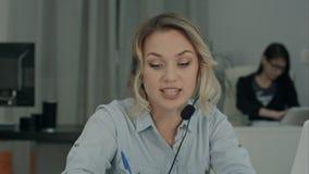 Młody żeński kierownik w słuchawki ma biznesową dyskusję przez laptopu Obraz Stock