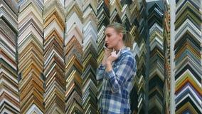 Młody żeński klient opowiada o obrazek ramy szczegółach przez smartphone w atelier Obraz Stock