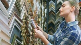 Młody żeński klient patrzeje dla ramy w specjalnym sklepie Obrazy Stock
