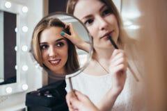 Młody żeński klient patrzeje w lustrze podczas gdy makeup artysta pracuje na jej brwiach w piękno salonie fotografia stock