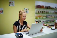Młody żeński konsultant używa książkę sprawdzać dla zdrojów produktów podczas gdy stojący w apteki wnętrzu, obrazy royalty free