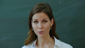 Młody żeński nauczyciel mówi ciekawić klasa blisko blackboard zbiory wideo