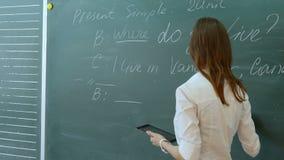 Młody żeński nauczyciel opowiada grupować na angielskiej lekci w szkolnej sala lekcyjnej zdjęcie wideo