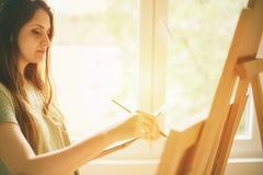 Młody żeński obraz na sztaludze zdjęcie stock