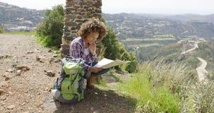 Młody żeński obsiadanie z plecakiem i mapą Obraz Royalty Free