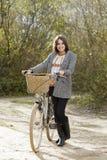 Młody żeński odprowadzenie z bicyklem w parku Zdjęcia Stock