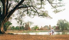 Młody żeński podróżnik weared lekki lato odzieżowy i kapeluszowy wczesnego poranku spacer z bicyklem wewnątrz blisko Ayutthaya dz obrazy stock
