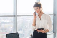 Młody żeński pomocniczy odpowiadanie biznesu wezwanie, mienia pda, dyskutuje praca szczegóły na telefonie komórkowym obrazy royalty free