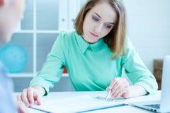 Młody żeński pracownik nadziewanie agencja pomaga wypełniać out formę męska osoba poszukująca pracy zdjęcia stock