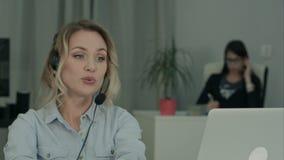 Młody żeński pracownik robi wideo wezwaniu przez laptopu w biurze zbiory