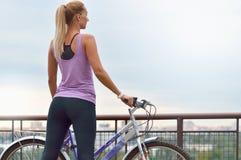 Młody żeński rowerzysta patrzeje miasto obok jej roweru Obrazy Royalty Free