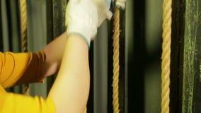 Młody żeński scena pracownik w rękawiczkach stawia górę na podnośnym mechanizmu teatr zasłona na kablu zbiory