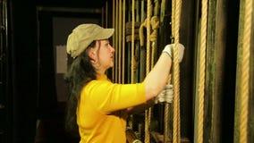 Młody żeński scena pracownik w rękawiczkach usuwa górę od kablowego podnośnego mechanizmu teatr zasłona zdjęcie wideo