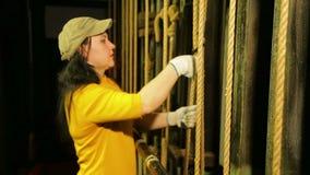 Młody żeński scena pracownik w rękawiczkach usuwa górę od kablowego podnośnego mechanizmu teatr zasłona zbiory