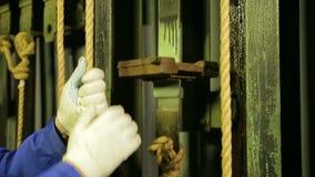 Młody żeński scena pracownik w rękawiczkach usuwa górę od kablowego podnośnego mechanizmu teatr zasłona zbiory wideo