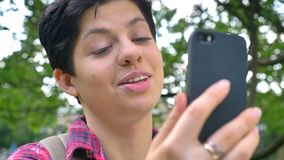 Młody żeński student collegu z krótkim czarni włosy ma wideo gadkę przez telefonu, ono uśmiecha się, outdoors dzień zbiory wideo