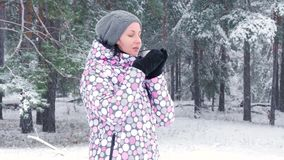 Młody żeński turysta pije gorącej herbaty podczas opad śniegu w zima lesie Pojęcie aktywny odtwarzanie, turystyka zbiory wideo