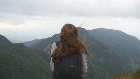 Młody żeński turysta z plecakiem cieszy się pięknego widok w górach Kobieta podróżnika pozycja na krawędzi zbiory wideo