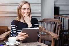 Młody żeński uczeń gawędzi na cyfrowej pastylce z przyjacielem podczas gdy siedzący w kawiarni, zdziwiony piękny kobiety używać Zdjęcia Royalty Free