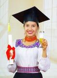 Młody żeński uczeń jest ubranym tradycyjną bluzkę z skalowanie kapeluszem, trzyma formalną papierową dyplom rolkę, szampański szk Obraz Royalty Free