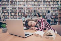 Młody żeński uczeń jest zmęczony i śpi przy desktop, on obraz royalty free
