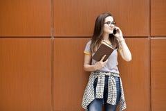 Młody żeński uczeń opowiada na telefonie wewnątrz outdoors zdjęcia stock