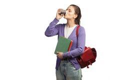 Młody żeński uczeń pije kawę z książkami i plecakiem Fotografia Royalty Free