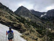 Młody żeński wycieczkowicz żegluje lasy, skalistej góry teren i śnieg, zakrywał doliny Skaliste góry obraz royalty free