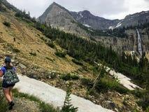 Młody żeński wycieczkowicz żegluje lasy, skalistej góry teren i śnieg, zakrywał doliny Skaliste góry zdjęcia stock