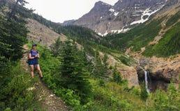 Młody żeński wycieczkowicz żegluje lasy, skalistej góry teren i śnieg, zakrywał doliny Skaliste góry obrazy royalty free